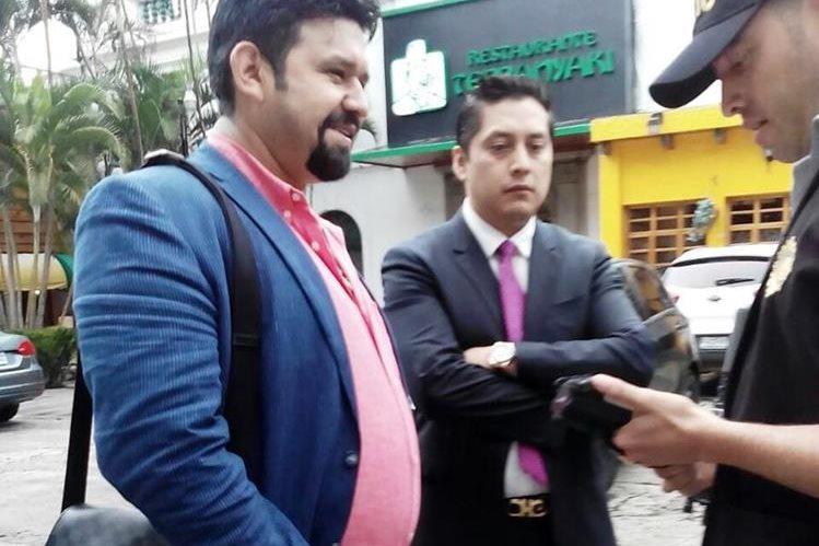 Un agente de la Policía procede a identificar al supuesto narcotráficante, Manuel Felipe Arenales Monroy, observa el abogado Mario Cano. (Foto Prensa Libre)
