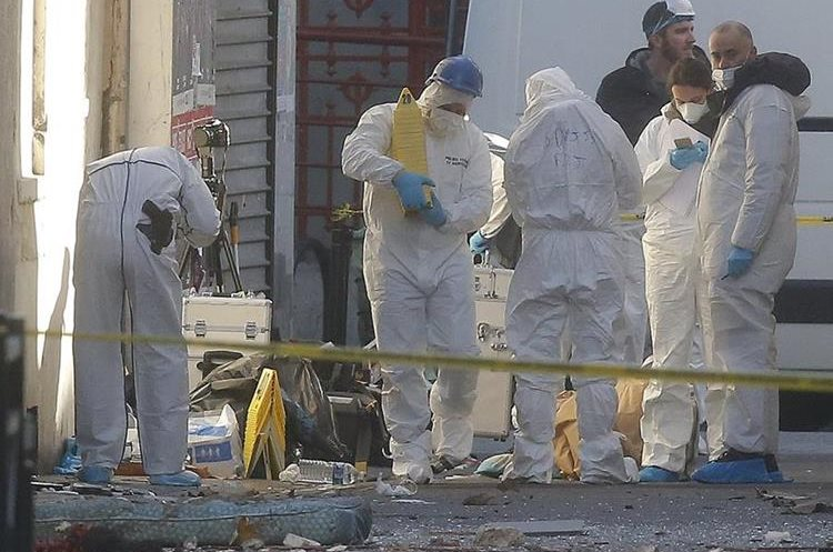 Forensic experts examine the scene in Saint-Denis, near Paris, Wednesday, Nov. 18, 2015. A woman wearing an explosive suicide vest blew herself up Wednesday as heavily armed police tried to storm a suburban Paris apartment where the suspected mastermind of last week