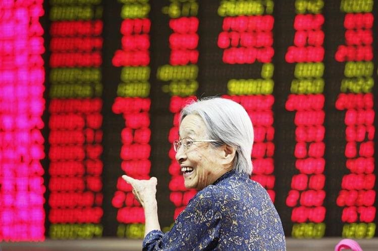 Una inversionista sonríe al ver los indicadores hoy en la bolsa de Pekín. (PL-EFE)