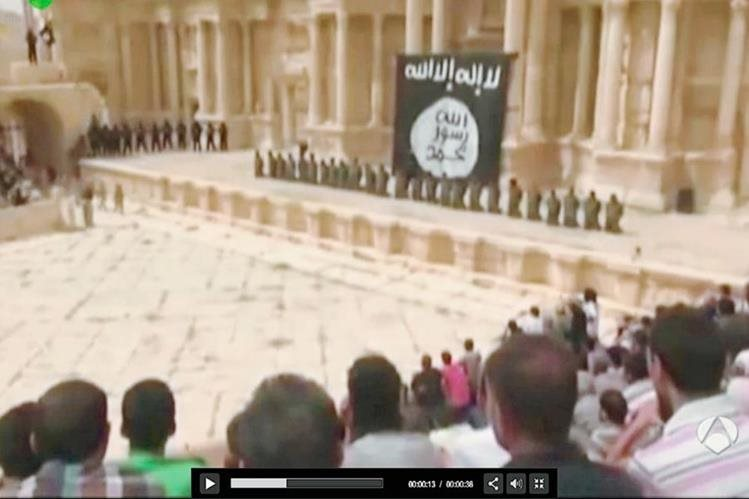 Captura del video yihadista que muestra a decenas de sirios en Palmira observando el macabro espectáculo. Al fondo los soldados de rodillas. (Antena 3).