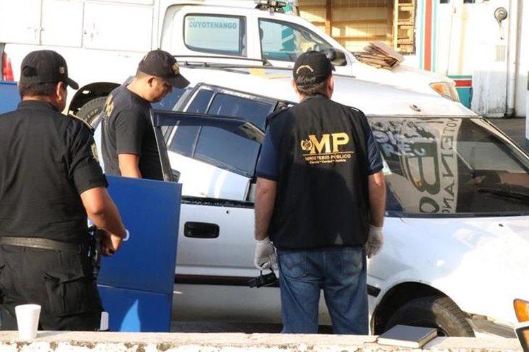 Fiscales del Ministerio Público revisan el taxi que transportaba a la comerciante muerta. (Foto Prensa Libre: Cristian Soto)