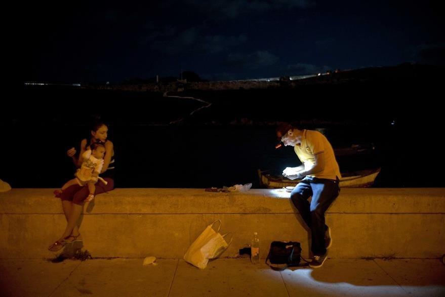 Un pescador prepara sus herramientas en compañía de su familia para ganarse el sustento diario en La Habana, Cuba. (Foto Prensa Libre: AP).