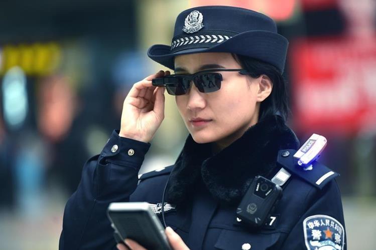 Una agente policial de Zhengzhou, Henan, China, utiliza el sistema de reconocimiento facial con el que se identifica a miles de personas con solo tomar una imagen. (Foto Prensa Libre: AFP)