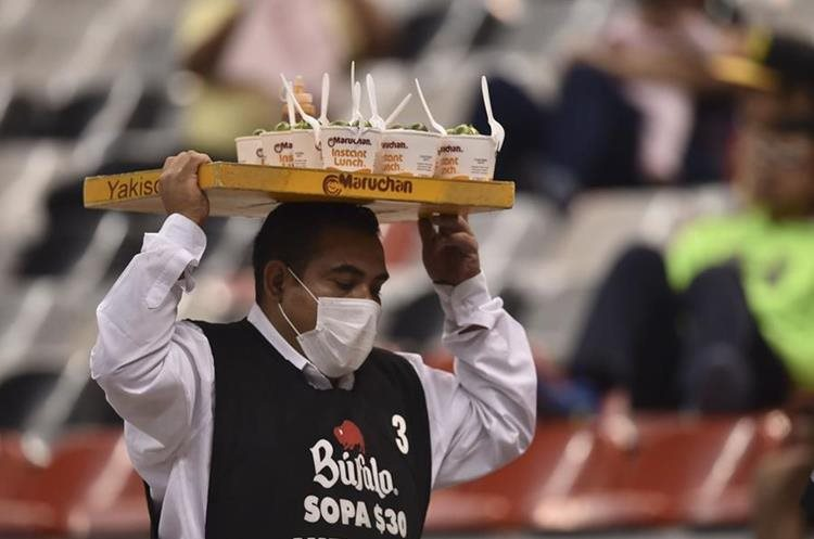 A vendor, his face covered with a surgical mask, is seen in the stands before the CONCACAF Champions League semifinal football match between Club America and Santos at the Azteca stadium in Mexico City on April 5, 2016.   The environmental authorities in Mexico City will keep 40 percent of cars off the roads on April 6, 2016 because of extremely high pollution levels, officials said.  / AFP PHOTO / YURI CORTEZ