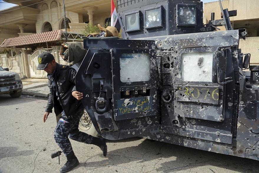Un policía desciende de una patrulla que muestra múltiples impactos de bala en Mosul. (Foto Prensa Libre: AP)