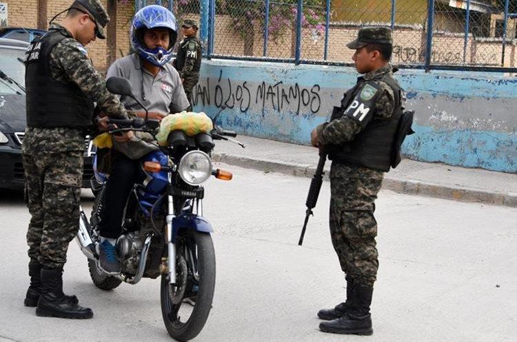 Efectivos la policía piden la identificación a un hondureño en el barrio el Bosque. (Foto Prensa Libre:AFP).