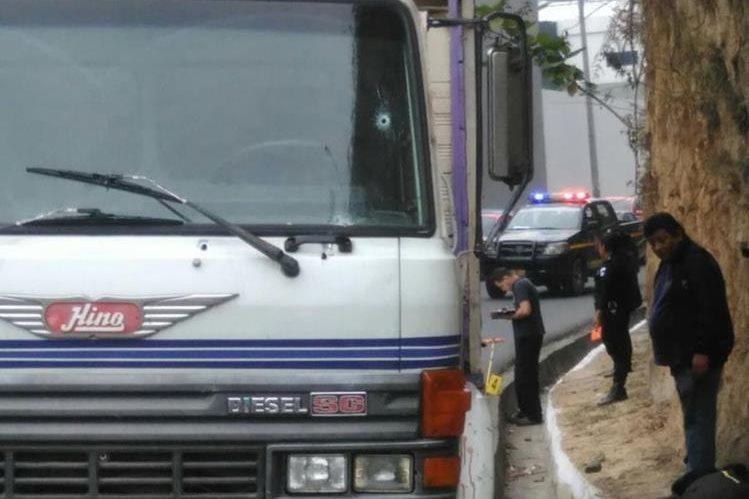 Peritos del MP recogen envidencia alrededor del camión, en la zona 18. (Foto Prensa Libre: Estuardo Paredes)