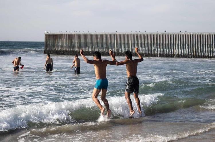 Migrantes centroamericanos corren a bañarse al llegar a las playas de Tijuana. (Foto Prensa Libre: AFP)