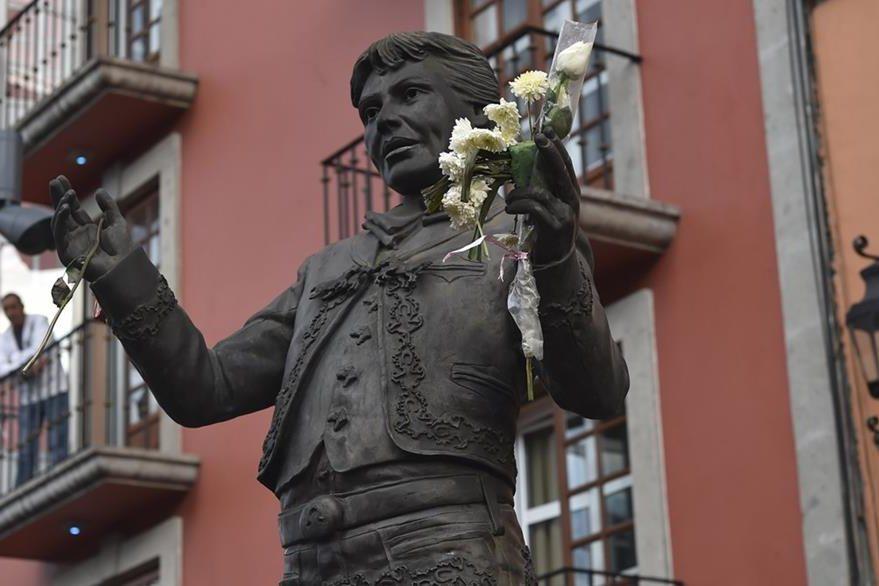 Seguidores de Juan Gabriel asisten a la Plaza Garibaldi y dejan rosas en una estatua del fallecido cantante y compositor mexicano. (Foto Prensa Libre: AFP)