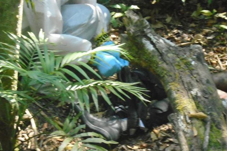 Un técnico del MP revisa el cuerpo del turista polaco Mikolaj Kurkiewigz que fue hallado en Tikal. (Foto Prensa Libre: Rigoberto Escobar)