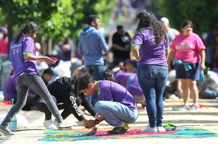 Voluntarios dan los últimos toques a la alfombra de aserrín.