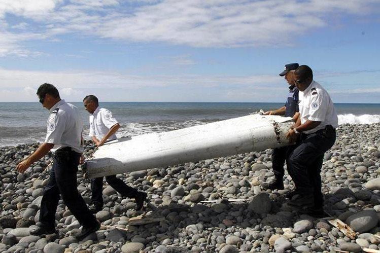 Oficiales cargan la parte de un ala, hallada en la isla francesa de la Reunión. (Foto: EFE).