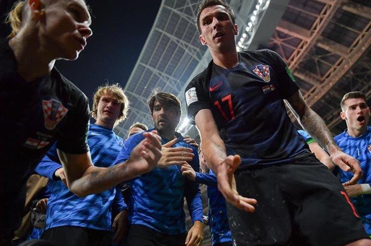Mario Mandzukic ofrece ayuda al fotógrafo Yuri Cortez para levantarse del cesped.