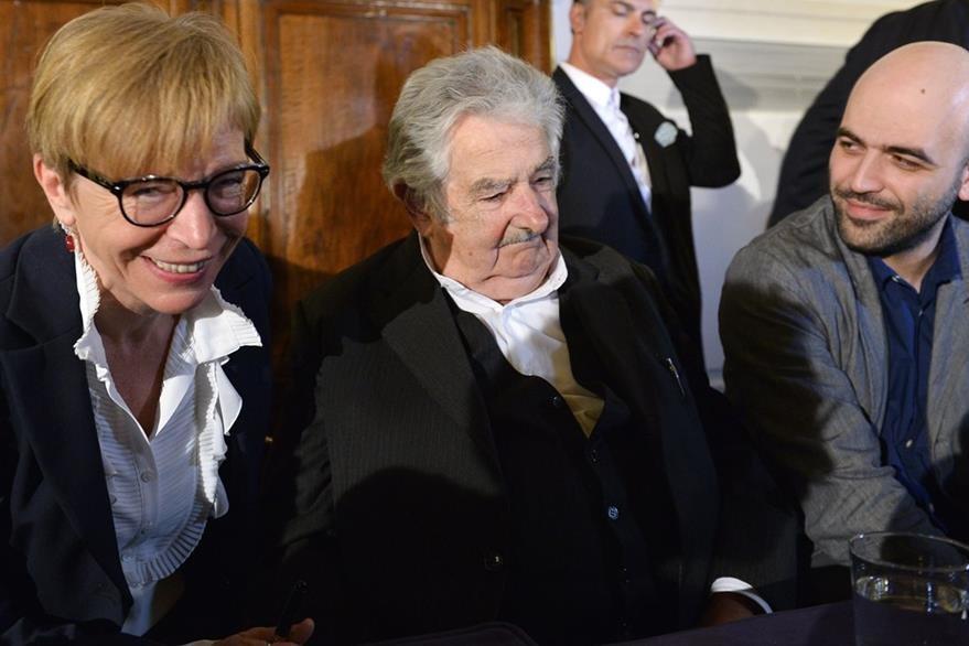 Mujica -centro- junto a dos periodistas en la presentación de su libro en Italia. (Foto Prensa Libre: AFP).