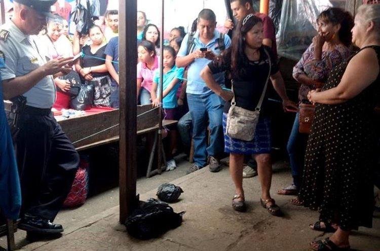 Curiosos observan la bolsa que contiene los restos del recién nacido que dejaron abandonado dentro de una mochila. (Foto Prensa Libre: Hugo Oliva)