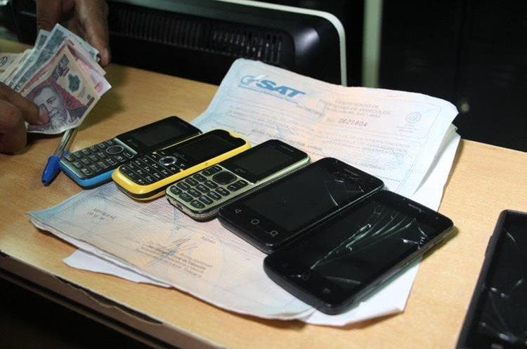 Junto con el dinero, la PNC consigno cinco celulares, títulos de propiedad de vehículos y el dinero que momentos antes habían cobrado. (Foto Prensa Libre: PNC)