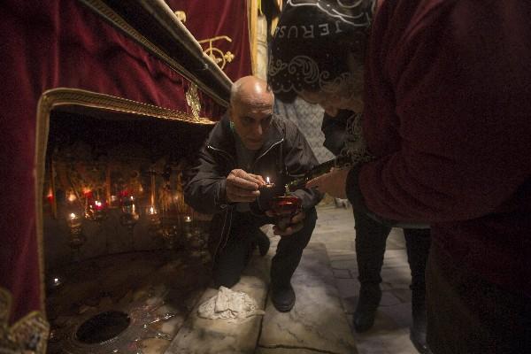 Personal de la iglesia llena una lámpara con aceite en la gruta de la Basílica. (EFE).