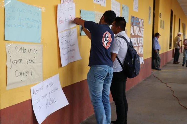 Estudiantes pegan rótulos en señal de protesta contra la administración municipal. (Foto Prensa Libre: Mike Castillo).