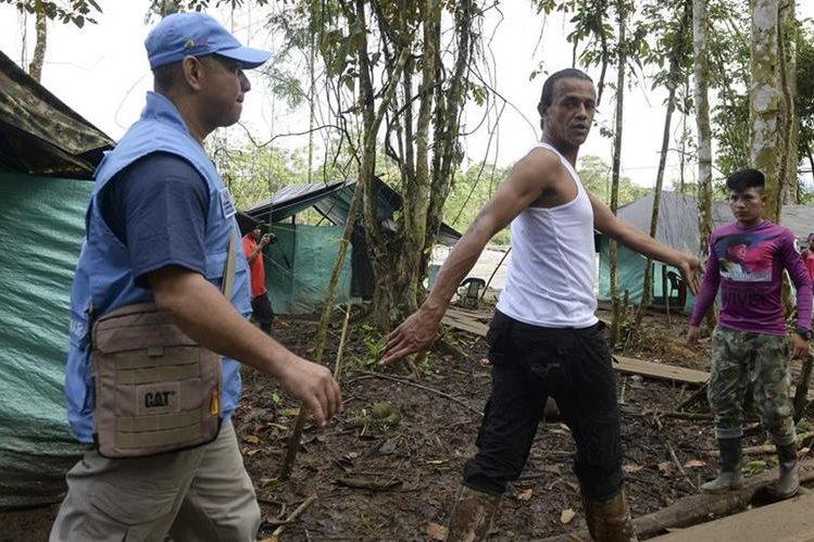 Un observador de la ONU camina junto con un guerrillero durante una revisión. (Foto Prensa Libre: AFP).