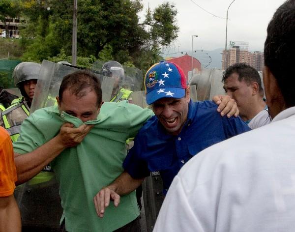 Henrique Capriles (c) reacciona a los efectos del gas pimienta.(AFP).