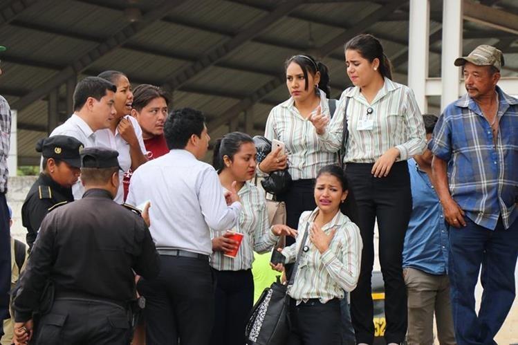 Compañeros de trabajo del joven asesinado, consternados en el lugar de los hechos. (Foto Prensa Libre: Mario Morales)