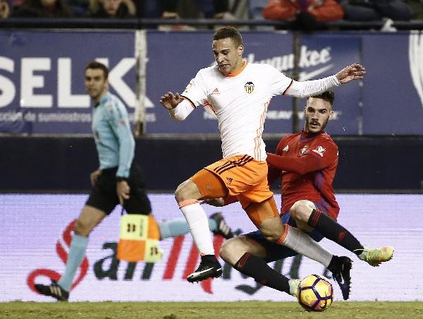 El delantero del Valencia, Rodrigo, intenta superar la entrada del defensa de Osasuna, Unai García. (Foto Prensa Libre: AFP).