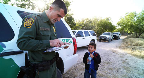 Un niño que recién llega a la frontera sur de EE. UU. es registrado por un oficial de la Patrulla Fronteriza de ese país. (Foto Prensa Libre: Hemeroteca PL).