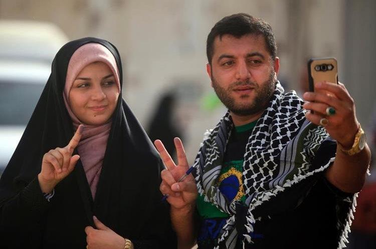 Ataviadas con sus velos, las mujeres hacen fila para acudir a ejercer su derecho al voto.