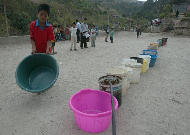 El agua es un bien cada vez más escaso. En la fotografía decenas de familias en un asentamiento de Guatemala esperan un camión que les abastezca del vital líquido. (Foto Prensa Libre: Hemeroteca PL).