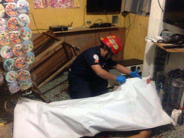 Un bombero Municipal cubre el cadáver del comerciante. (Foto Prensa Libre: CBM)