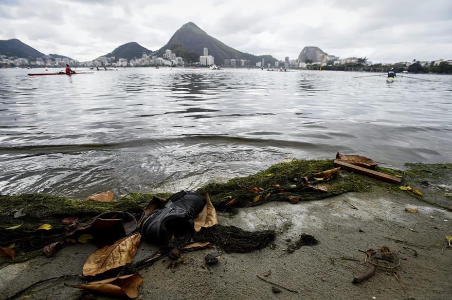 La basura se aprecia durante un entrenamiento de remeros en la laguna Rodrigo de Freitas.(EFE).