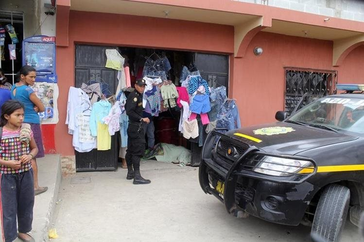 Vecinos de la cabecera de Jalapa y un agente policial observan cadáver baleado de mujer. (Foto Prensa Libre: Hugo Oliva)