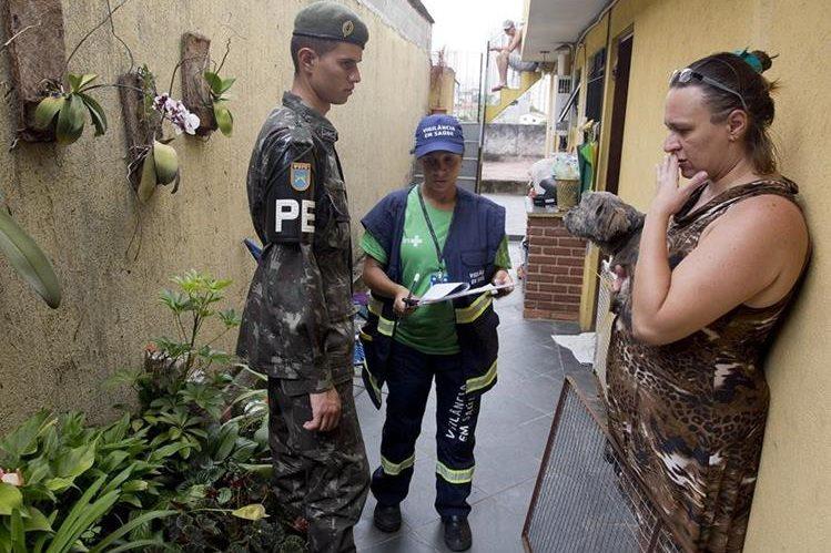 Un soldado y un trabajador de Salud entrevistan a una mujer en Sao Paulo, Brasil. (Foto Prensa Libre. EFE).