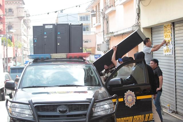 Agentes de la PNC cargan una autopatrulla con artículos que se encontraban dentro de la sede. (Foto Prensa Libre: Erick Ávila)
