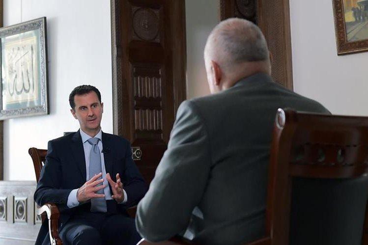 El presidente sirio, Bashar al Asad, (de espaldas), conversa con el periodista de la agencia rusa RIA Novosti. (Foto Prensa Libre: AFP).