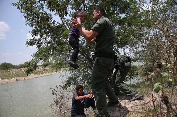 Un agente de la Patrulla Fronteriza pone a salvo a una niña mientras cruzaba con su familia el Río Grande. (Foto Prensa Libre: Hemeroteca PL)
