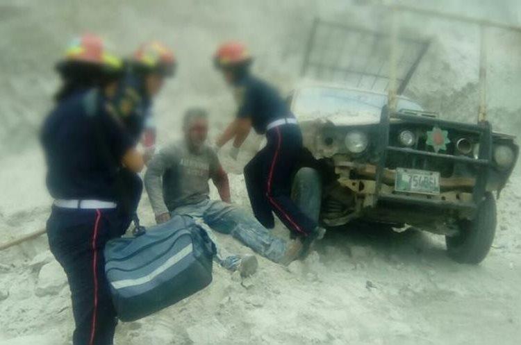 Socorristas atienden a uno de los hombres que quedó soterrado luego de que se derrumbara el paredón de donde extraían tierra. (Foto Prensa Libre: Hugo Oliva)