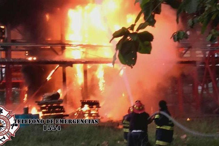 Bomberos luchan por sofocar las llamas del incendio que consumió la bodega de una fábrica de pintura en Masagua, Escuintla. (Foto Prensa Libre: cortesía de Bomberos Municipales Departamentales)
