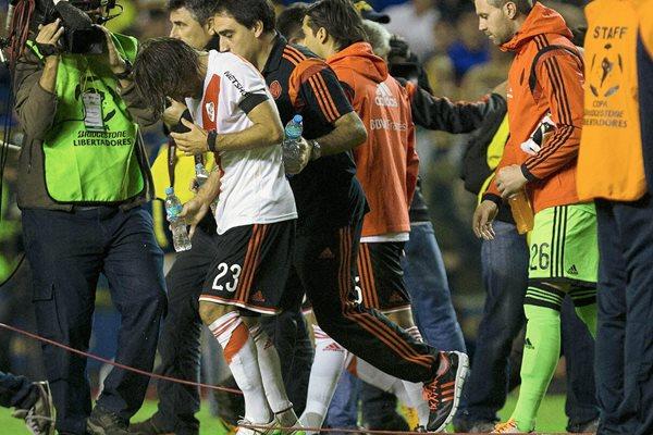 Leonardo Ponzio de River Plate es asistido al salir del túnel, después del juego suspendido en la Bombonera. (Foto Prensa Libre: Hemeroteca PL)