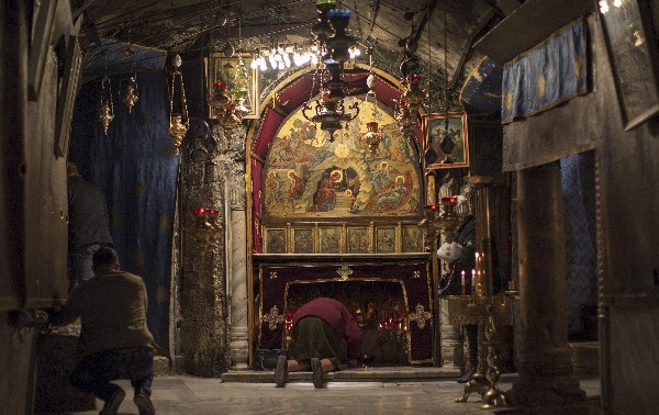 Un devoto reza en la gruta de la Basílica de la Natividad. (EFE).
