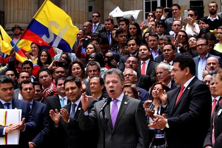 El presidente Juan Manuel Santos (segundo de derecha a izquierda), da declaraciones luego de entregar el acuerdo al Congreso. (Foto Prensa Libre: AFP).