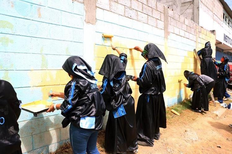 Grupo de encapuchados de la Facultada de Humanidades del Cunoc pintan la pared de la Escuela Oficial de Párvulos Lucas T. Cojulun, en Quetzaltenango. (Foto Prensa Libre: Carlos Ventura)