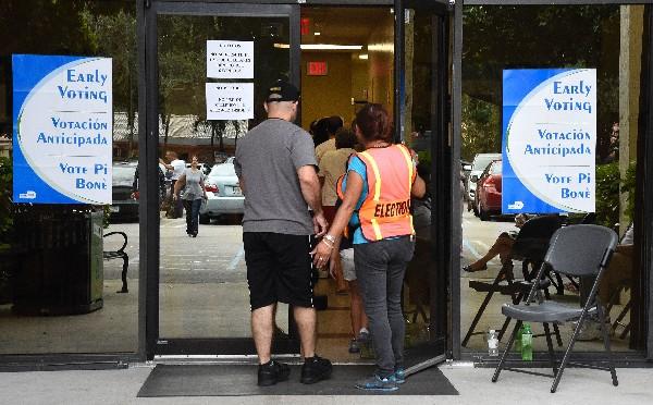 Varias personas acuden a votar en un centro de votación en Miami.(AFP).