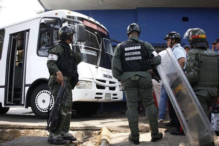Oficiales venezolanos custodian el bus que atropelló a los policias. (Foto Prensa Libre: AFP).
