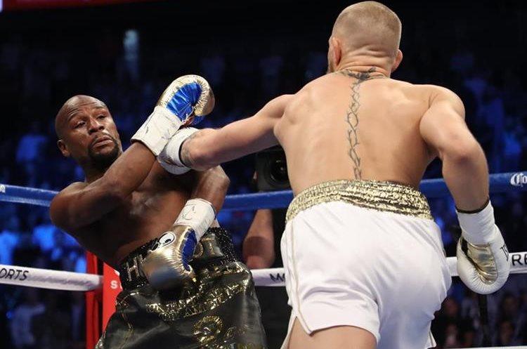 Floyd Mayweather Jr. esquiba un golpe de Conor McGregor.