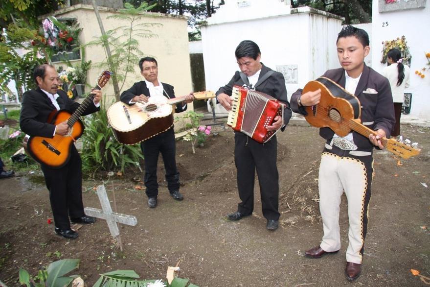 Familiares llevan  grupos musicales a las tumbas de sus finados para que interpreten  melodías, en cementerios de  Sacatepéquez. (Foto Prensa Libre: Renato Melgar)