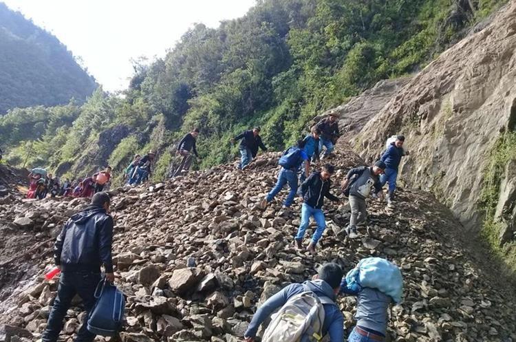 Un grupo de vecinos camina sobre las piedras que cayeron a la ruta en Vuelta al Aire, Chajúl, Quiché. (Foto Prensa Libre: Héctor Cordero)