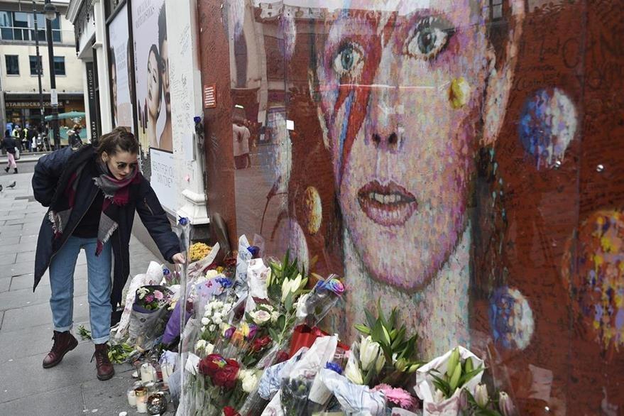 Seguidores de Bowie dejan flores junto al mural del artista en Londres, en el primer aniversario de su muerte. (Foto Prensa Libre: EFE)