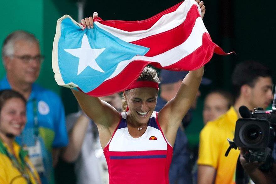 Mónica Puig alza la bandera de Puerto Rico luego de coronarse en el tenis femenino olímpico. (Foto Prensa Libre: AP)