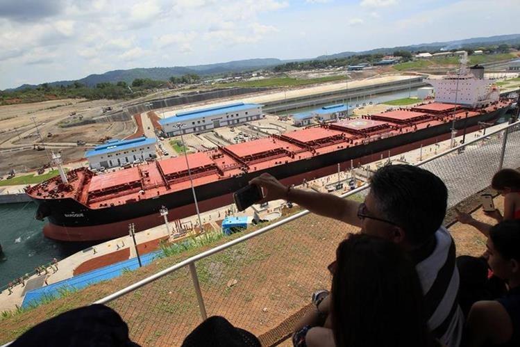 Un grupo de personas observa el paso del primer buque. (Foto Prensa Libre: EFE)